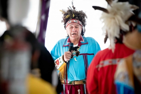 A man in regalia speaks into a microphone at an event