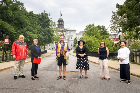 Une photo de conférenciers debout devant le Pavillon des arts de McGill lors de la cérémonie de levée du drapeau de la ceinture Hiawatha Wampum