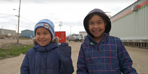 Two smiling young children dressed for cold weather