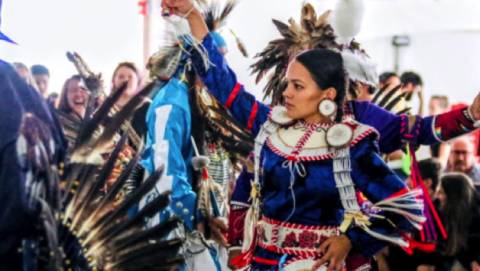 A photo of a female dancer in blue, red, and white regalia during a Pow Wow event