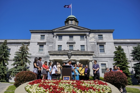 Students stand around a speaker at an outdoor podium, in front of a large building and behind a flowerbed