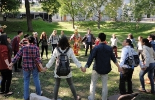 Students stand in a circle on the grass and hold hands