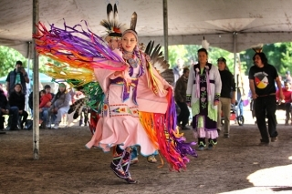 A female dancer in multi-coloured regalia performs at the McGill Pow Wow.