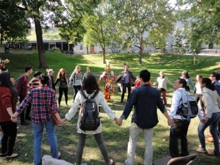 Students stand outdoors in a circle and hold hands as part of an activity at McGill