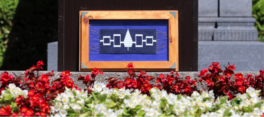 A framed Hiawatha Wampum Belt flag sits in front of a garden at McGill.