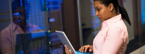 A woman looks at her PC while standing in front of a rack of servers