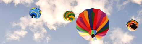 Multiple colourful hot air balloons in the blue sky