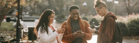 Three multiracial students using smartphones in a city park
