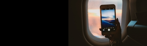 seated airplane passenger taking photo of scene outside window with smart phone
