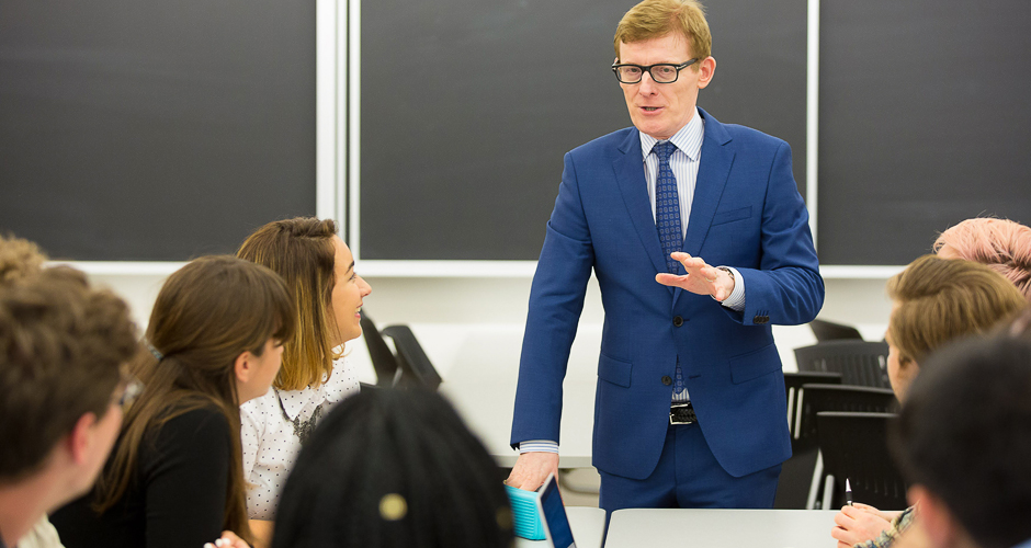 A professor speaking to a group of students in class. Photo by Owen Egan