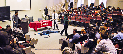 """Volunteers explaining the """"mock trial"""" activity to high school students, during their visit to McGill."""