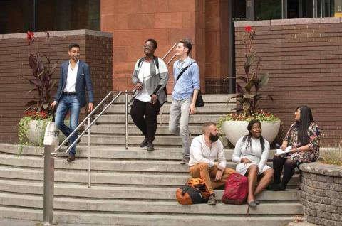 Des étudiant.e.s sur les escaliers de la bibliothèque de droit