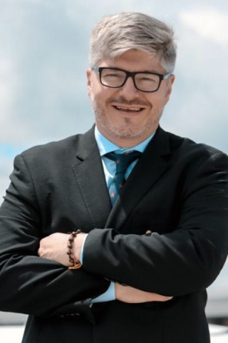 Juan Carlos Salazar, LLM 2000. Description: A white man with silver hair and dark framed glasses. He wear  a dark suit over a blue shirt. His arms are crossed. He is standing outside and smiling.
