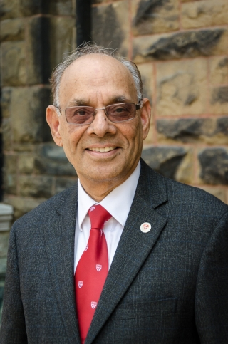 Professor Ram Jakhu (an Indian man wearing a gray jacket over a white shirt and red McGill tie stands in front of a stone wall). Photo by Lysanne Larose.