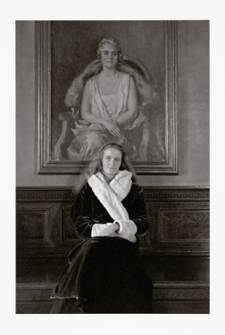Photo of a woman, sitting in a fur coat with hands folds in her lap in front of a painting of a woman in the same posture.