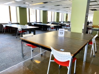 Large open room with multiple tables with numbers on them. Chairs are spaced apart.