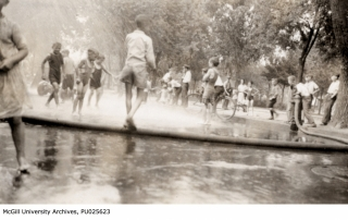black and white photo of chidlren playing in the spray of a fire hose