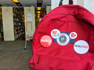 """Burgundy back pack with 5 buttons pinned to it with messages saying """"I love books"""" and #McGill24."""