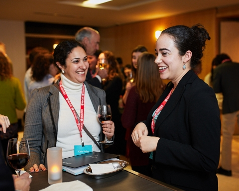 Two women chat at a Max Bell School conference