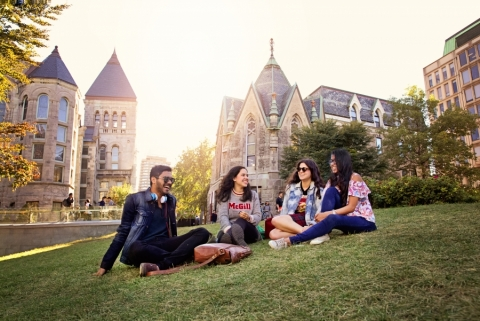 Four McGill students sitting on campus grounds grass