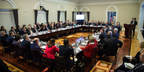 People seated around and behind a rectangular conference style table setting