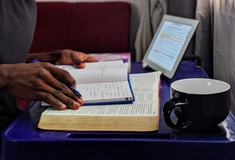 Hands taking notes while reading from book and tablet on a desk