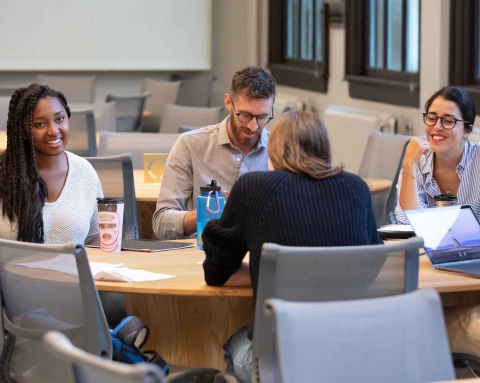 MPP students sit around a table and chat