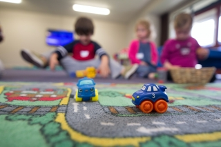 Children play with toys cars in a daycare
