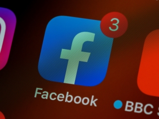 The Facebook app icon appears on an iPhone Home Screen