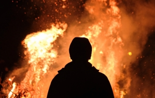 A man stands in front of a fire