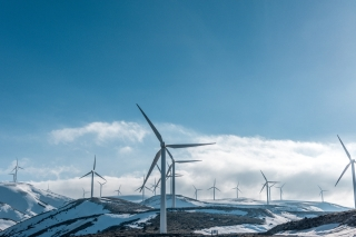 A photograph of wind turbines on snowy hills