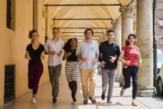 Students run together while smiling down a corridor