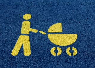 An symbol painted on asphalt depicts a parent pushing a stroller