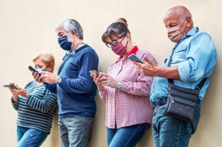 A line of people in masks look at content on their cell phones