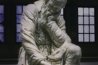 an image of the sculpture of a man who is sitting with his left hand supporting his face