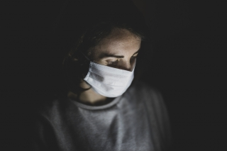 A woman wearing a medical mask stands in a dark room