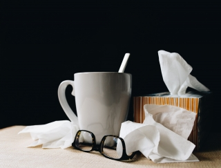 A mug of tea, a box of tissues, and a pair of glasses lay strewn out across a table