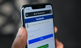 A person holds an iPhone with the Facebook login page open on its screen