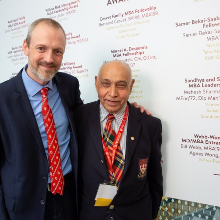 Alex King (Desautels Director of Development) and Mahesh Sharma (MEng'72, MBA'76) stand beside the sign posting the award donors and recipients.