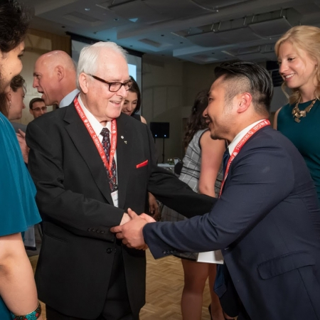 Marcel Desautels shakes soon-to-be MBA'18 graduate Jiawei Lin.