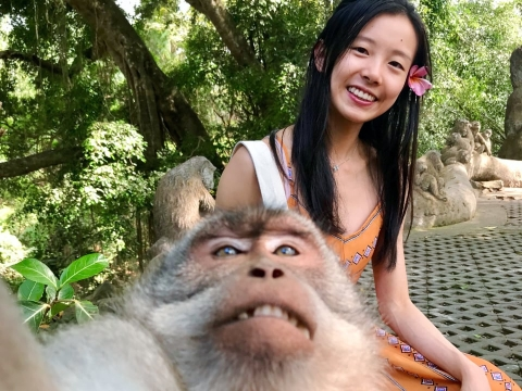 A student taking a selfie with a monkey