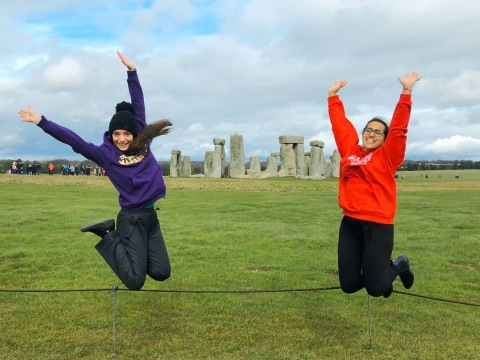 Two students jumping in front of Stonehenge