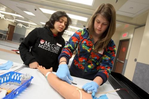 McGill Med-1 student Marina Ibrahim (left) shows high school student Kelsey Abbo
