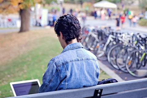 Student sitting on a bench on campus, working on computer