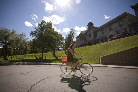 Student cycling on McGill campus in the summer