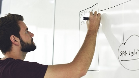 Teaching assistant writing on a whiteboard