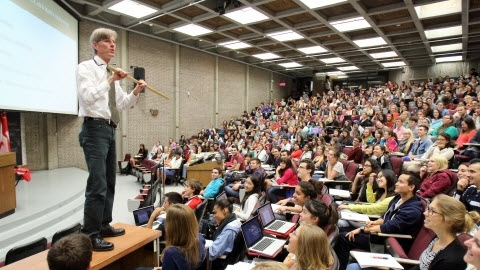 Instructor presenting in lecture hall with students listening