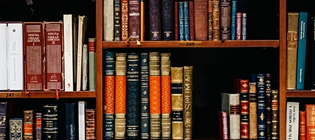 Old books stacked in library shelves.