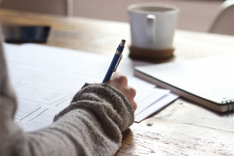 Right hand placed onto papers on desk with pen in writing pose, and with mug and notebook on the side.