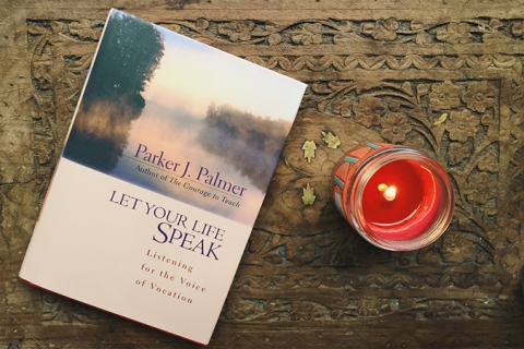 """Image of """"Let Your Life Speak"""" book by Parker J. Palmer on wooden desk surface next to red lit candle."""